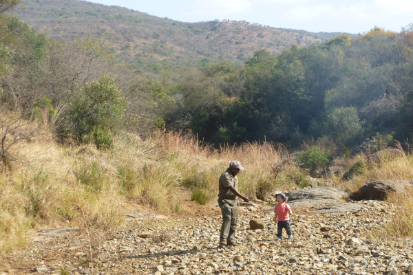 A ranger playing with a kid during a family safari